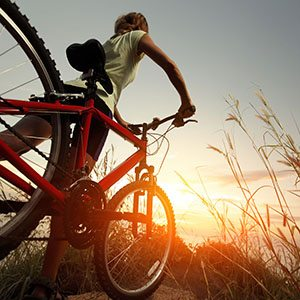 Young lady with bicycle on a rural road with grass; Shutterstock ID 130948919; PO: Zeus